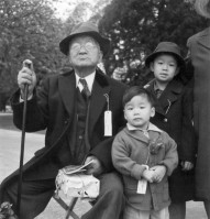 Grandfather and grandchildren awaiting evacuation bus. The grandfather conducted a dyeing and cleaning business. Hayward, California, 1942
