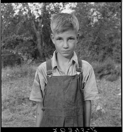 "Migratory boy in squatter camp. Has come to Yakima Valley for the third year to pick hops. Mother: ""You'd be surprised what that boy can pick."" Washington, Yakima Valley."