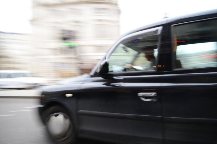 This is a high resolution digital image that has captured motion blur giving a sense of movement as the taxi banks a corner in London. How does the lack of sharp definition change your perception of the image? Is it a piece of documentary photography, or art?