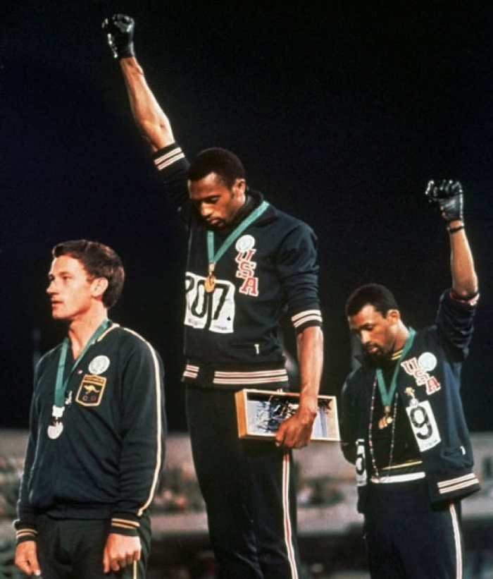 "AN OCT. 16, 1968, FILE PHOTO; EFE OUT @*@* FILE @*@* In this Oct. 16, 1968, file photo, United States athletes Tommie Smith, center, and John Carlos, right, extend their gloved fists skyward during the playing of the ""Star-Spangled Banner"" after Smith received the gold and Carlos the bronze for the 200-meter run at the Summer Olympic Games in Mexico City. Carlos and Smith raised their black-gloved fists on the medals stand as a symbol of protest 40 years ago at the Mexico City Olympics, creating an iconic image from the games. Australia's silver medalist Peter Norman is at left. (AP Photo/file)"