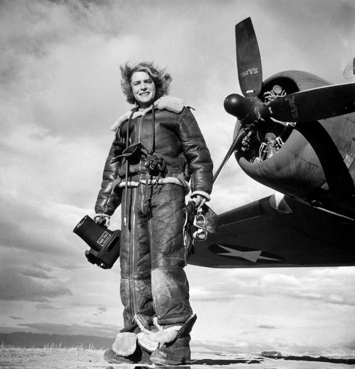 LIFE photographer Margaret Bourke-White clad in fleece flight suit while holding aerial camera, standing in front of Flying Fortress bomber in which she made combat mission photographs of the US attack on Tunis.